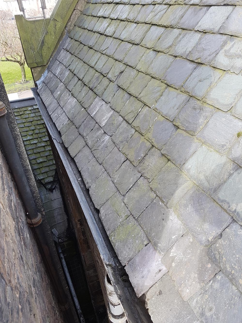 Looking along the newly fitted gutters with all the slates patched back in